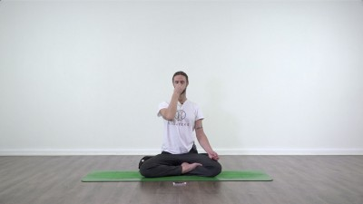 Yoga teacher performing yoga posture on green yoga mat on white background